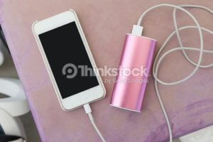 mobile phone in plastic case plugin to a power bank charger through a charging cable, on old pinkish purple outdoor plastic table